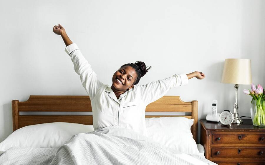 Young woman wakes up feeling motivated to stay motivated during pandemic.