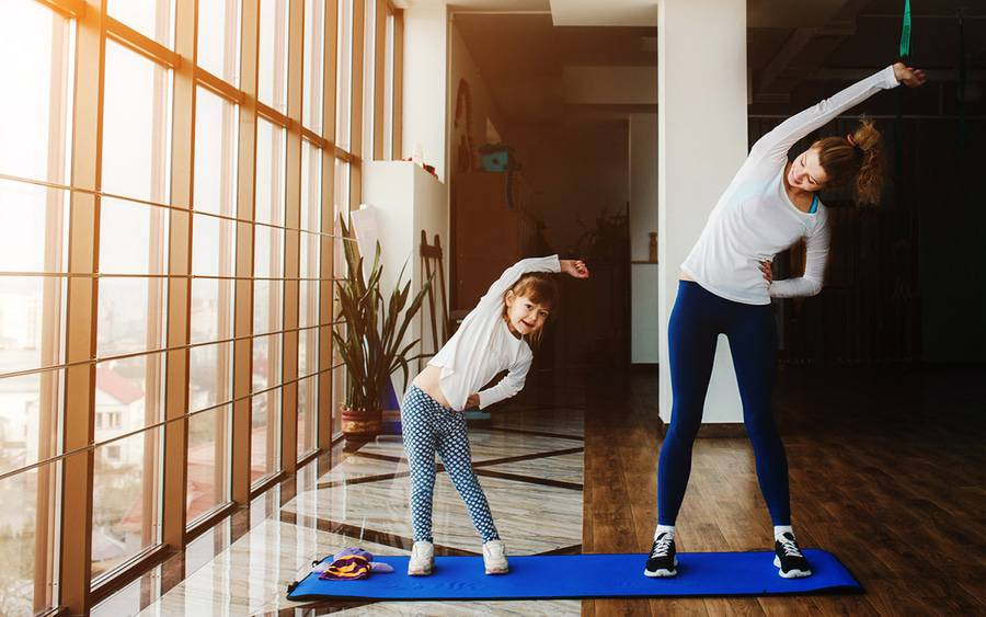 Mother teaching daughter how to exercise at home.