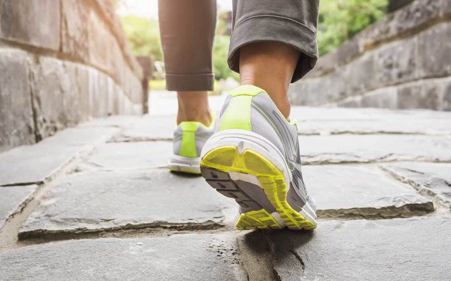 Close up shot of a woman's running shoes walking down a stone walkway.