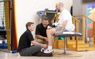 A patient sits on a physical rehabilitation chair as two therapists sit and kneel to make an adjustment to the patient's  shoes in a therapy setting.