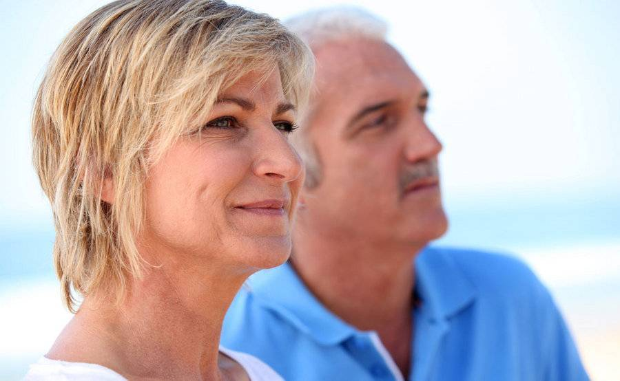 A smiling middle-aged couple on the beach represent the full life that can be led after skin cancer treatment.