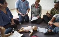 Adults learn infant CPR in a classroom.