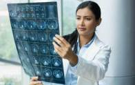 An imaging healthcare expert wearing a lab coat examines results from a patient MRI in a hospital setting