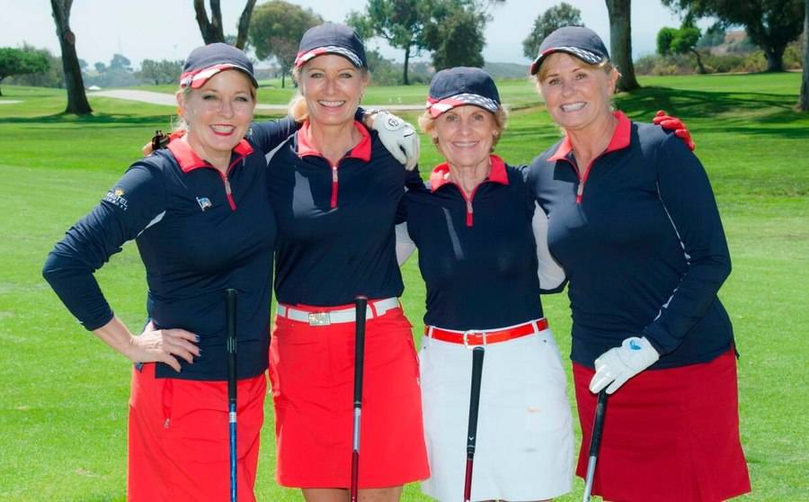 A foursome of mature female golfers smile for a photo at the Torrey Pine South Golf Course.