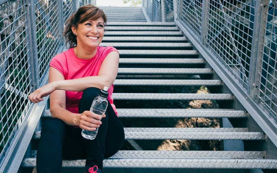 A woman rests on a stairway after a workout to stay fit.
