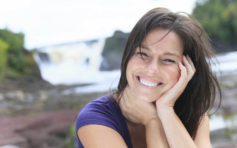 A relaxed woman smiling with a waterfall visible in the background