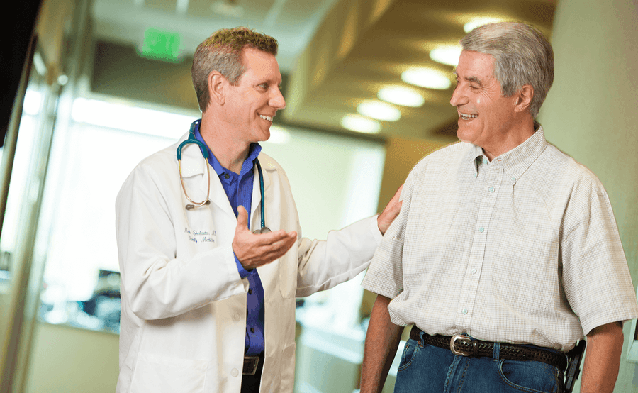 A Scripps physician talks with a mature male patient in a clinic hallway.