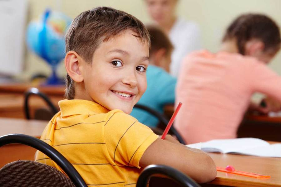 A smiling student diagnosed with ADHD turns around in his chair while working on an assignment in a classroom setting.