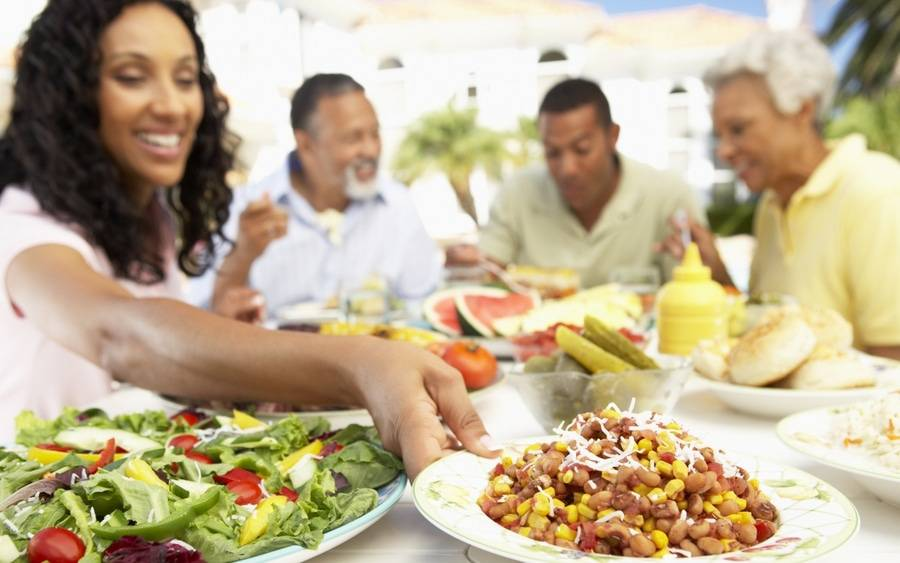 An African-American family eating heart-healthy meal with vegetables, fruits and legumes.