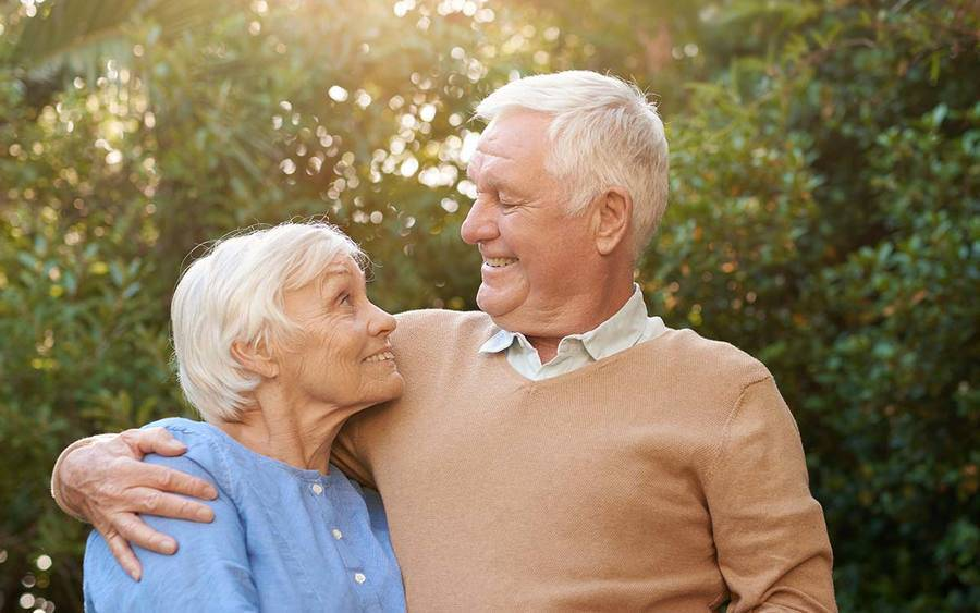 A smiling mature man and woman in their yard represent the improved quality of life with ALS treatment.
