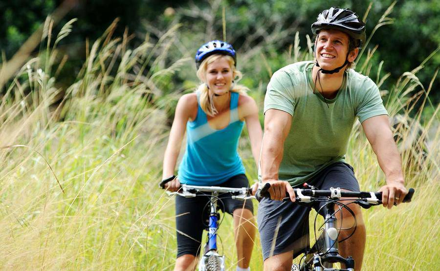 A woman and man riding bicycles together in tall grass.