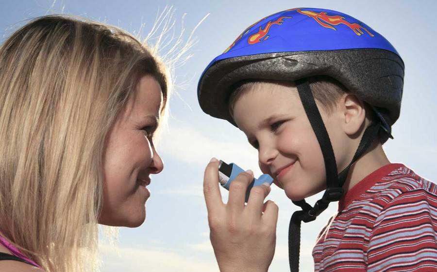 A smiling mother assists her son with an asthma inhaler in an outdoor environment.