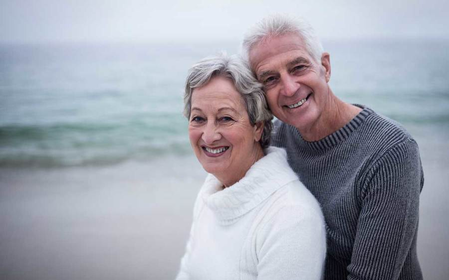 A man and woman in their senior years embrace in a beach setting on a cloudy day.