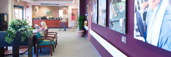 Image of a rehabilitation center waiting room, with colorful walls and artwork, potted plants and comfortable chairs.