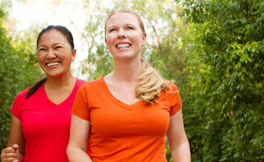 Two women smiling as the walk outdoors for exercise, representing the active lifestyle that people often enjoy after Roux-en-Y gastric bypass surgery.