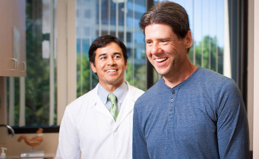 Scripps bariatric surgeon Mark Takata, MD, and a patient smiling in an exam room.