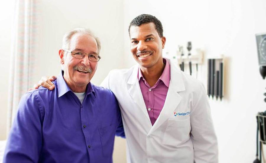 Scripps bariatric surgeon William Fuller, MD, stands with a patient after a follow up visit, illustrating the support services available after weight loss surgery.