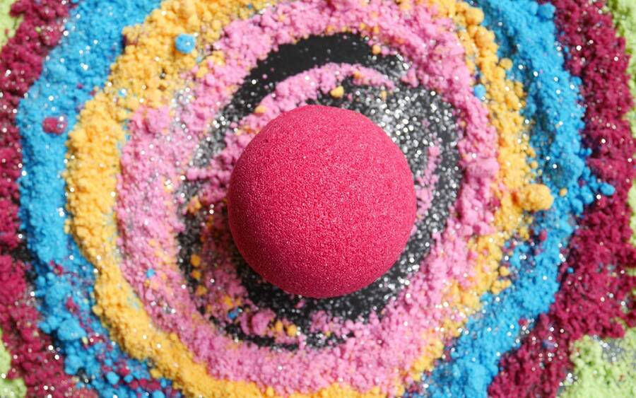 A bath bomb sits within a colorful swirl of the substances it's comprised of that may irritate your skin.