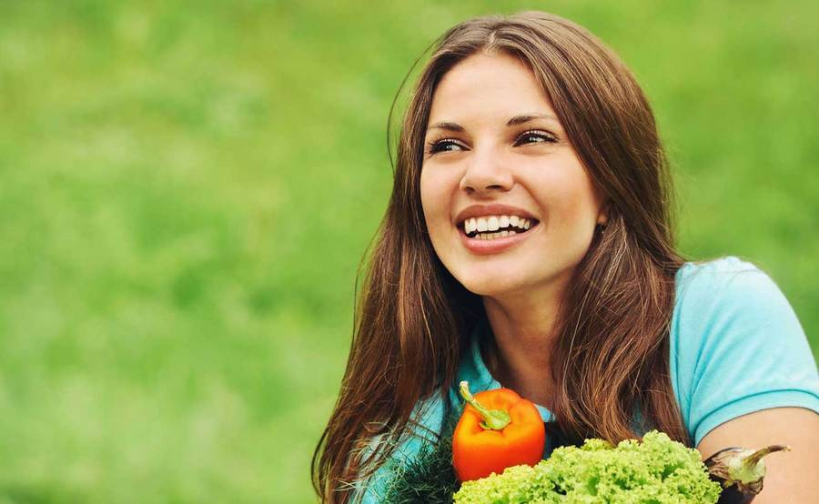 A smiling woman in a grassy field holds fresh produce in her arms.