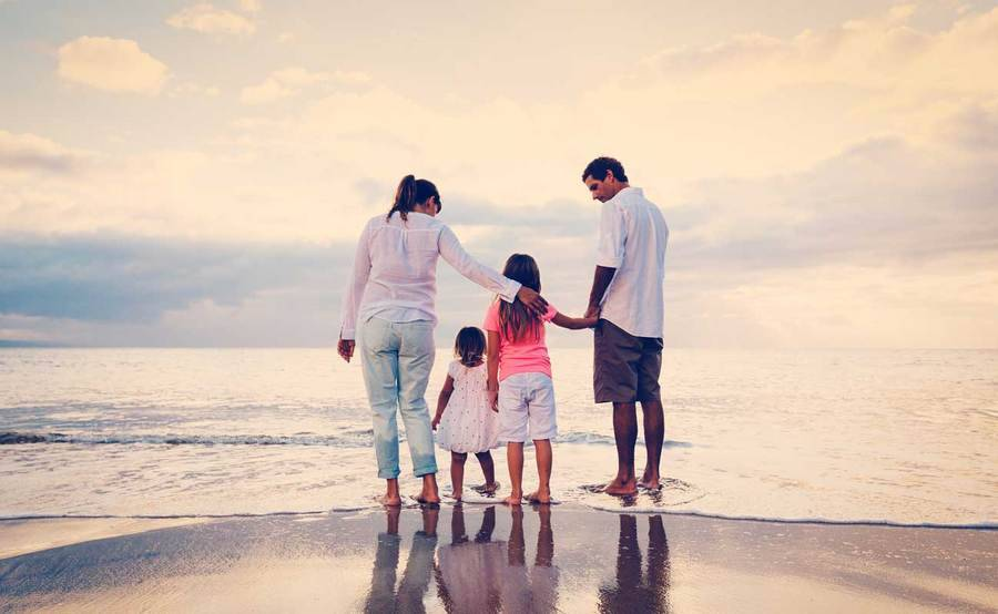 Man, woman and two small children stand on the ocean shoreline on a cloudy day.