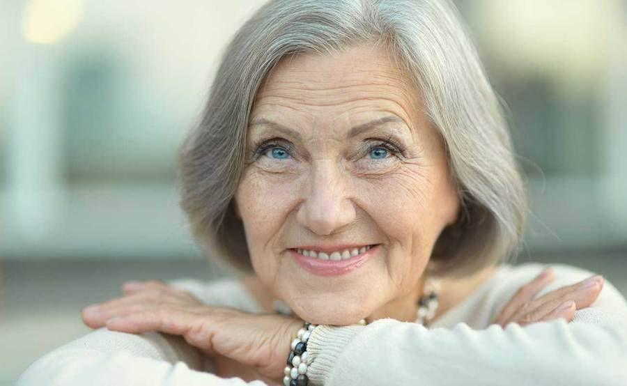 A smiling mature woman represents the full life that can be led after bile duct cancer treatment.