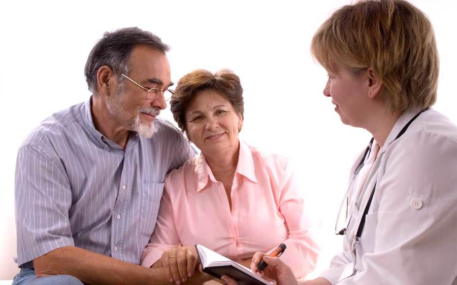 Two concerned patients have an engaging discussion with their physician in a clinical setting