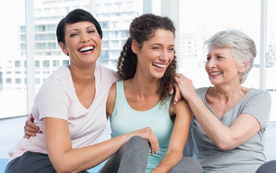 Three smiling women sit in a yoga studio, representing the active life that can be enjoyed after bladder symptoms are under control.