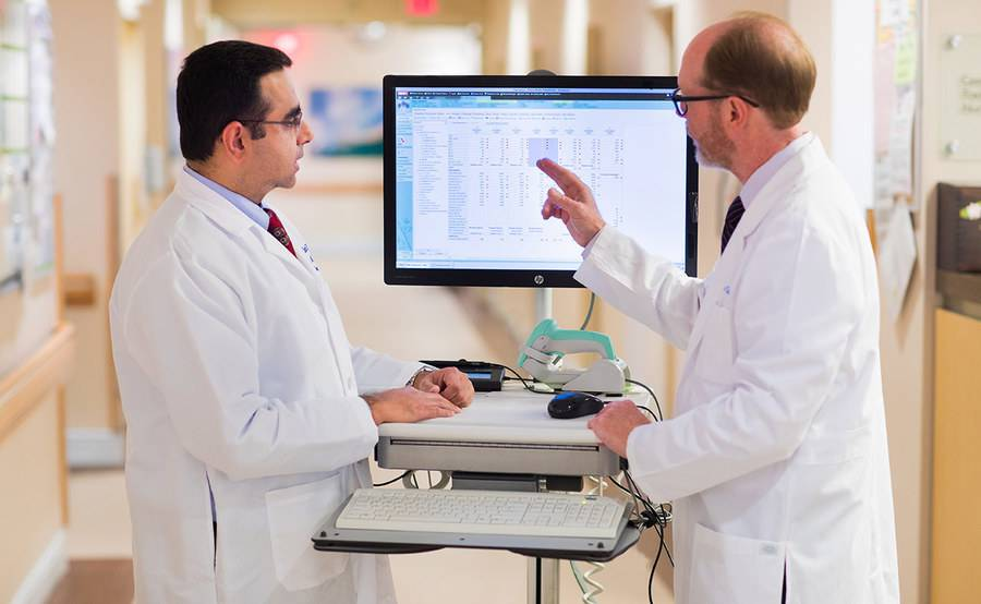 Drs. Anuj Mahindra and James Mason discuss medical information displayed on a screen, representing the advanced collaborative care at Scripps for blood and marrow transplant.