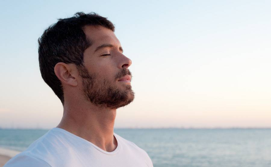 A man takes a deep breath on the beach, representing an improved quality of life with expert care for blood disorders.