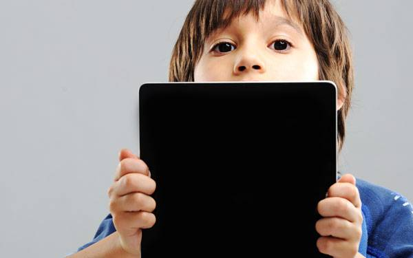 Young boy in blue t-shirt peering over a digital tablet he is holding with both hands.