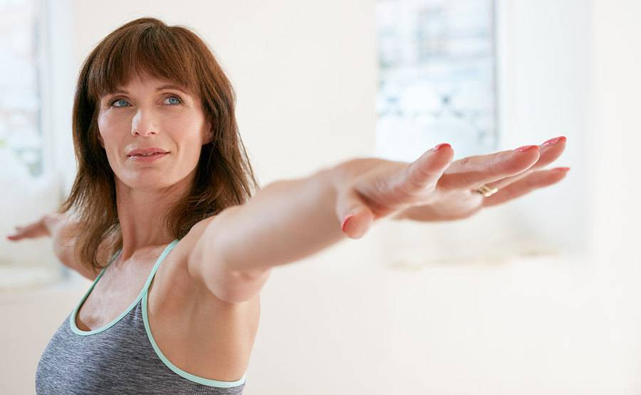 A peaceful middle-aged woman practices a yoga pose in a sports bra, representing the confidence gained from breast augmentation.