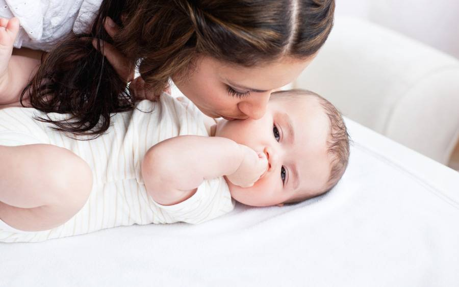 A woman gently kisses an infant on the cheek, representing the critical bonding time with a newborn.