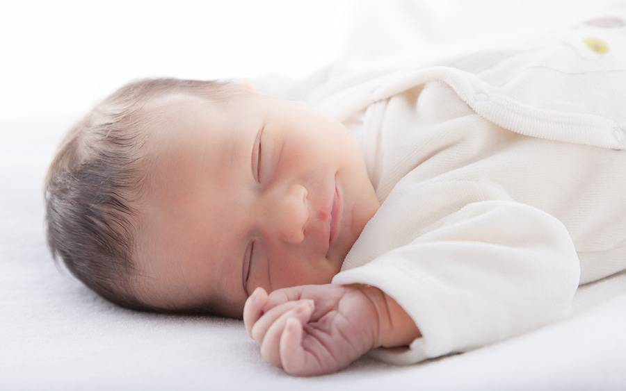 A smiling infant sleeps in a sleep sack.