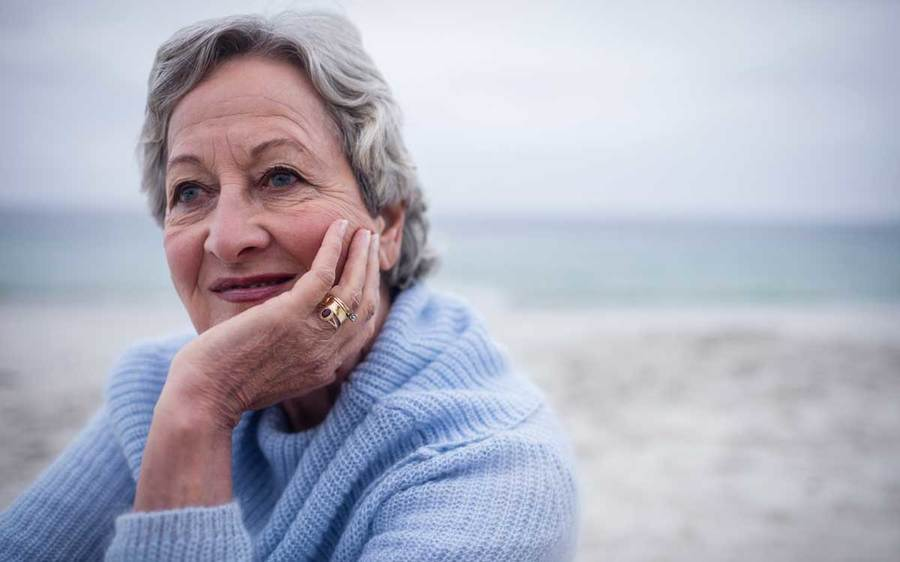 A thoughtful middle-aged woman rests at the beach with her chin in her hand
