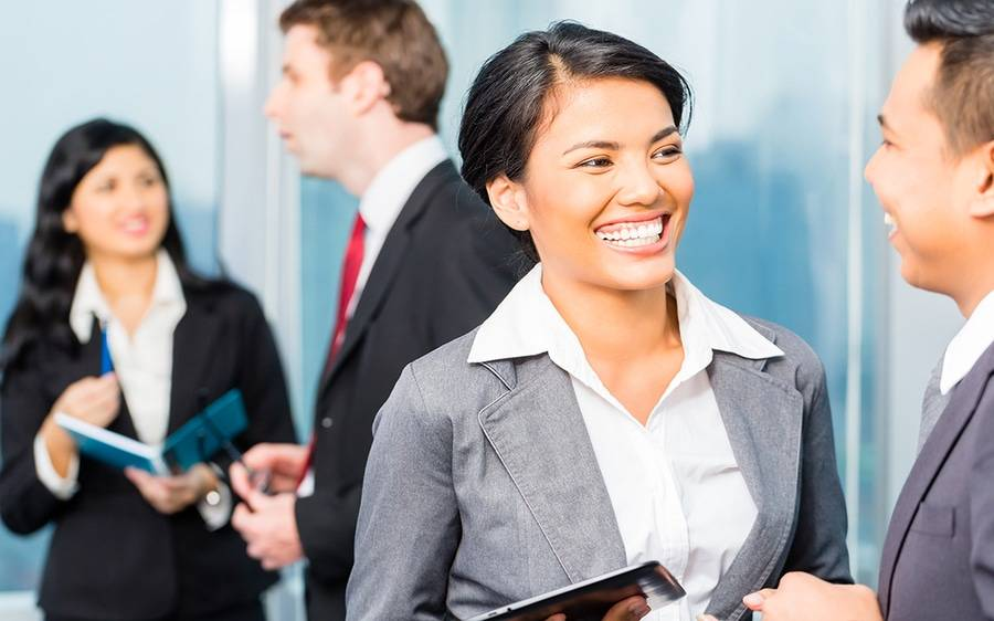 Woman in suit smiling and speaking with man
