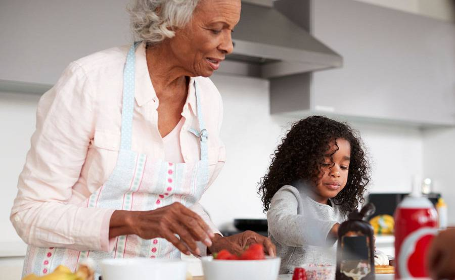 A mature woman prepares strawberries and waffles with her granddaughter, representing a healthier life with treatment for carotid artery disease.