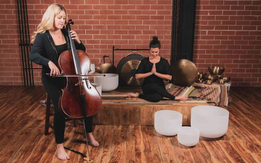 A woman plays a cello while another woman meditates near singing bowls.