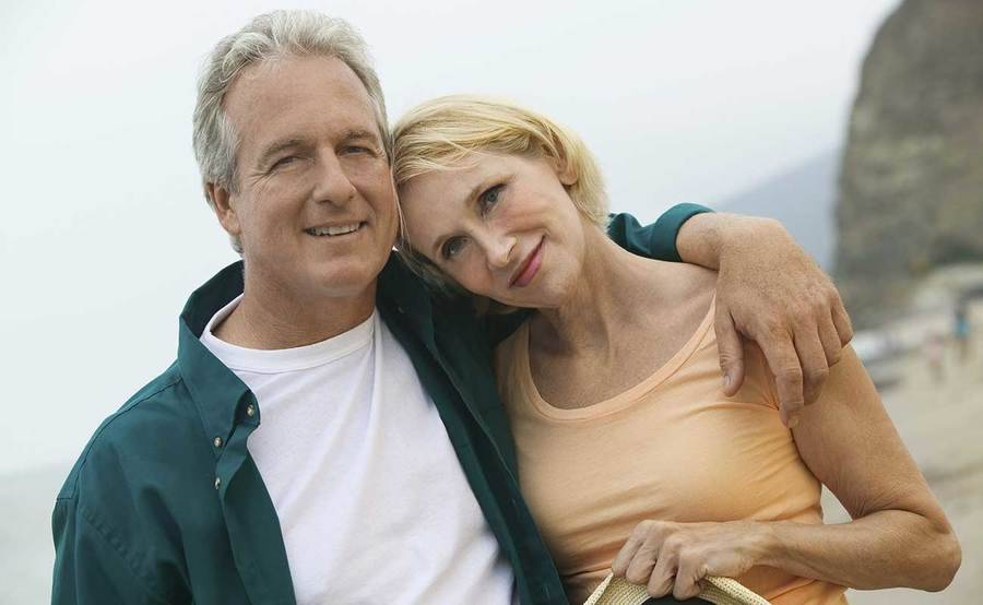 A smiling middle-aged Caucasian couple on the beach represents the full life that can be led with the latest chemotherapy techniques that maximize comfort.