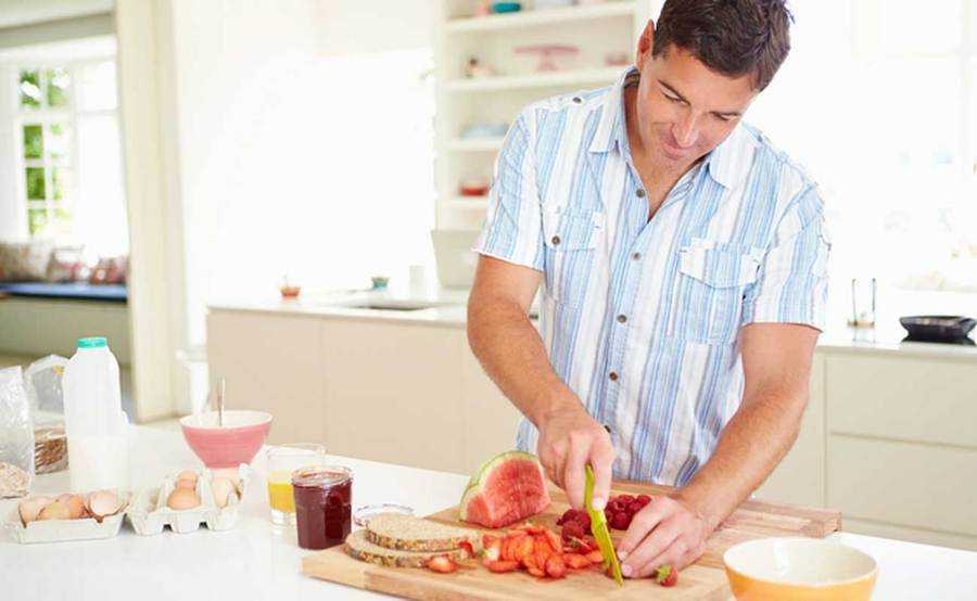 A healthy man slices berries for a low-cholesterol meal in his kitchen.