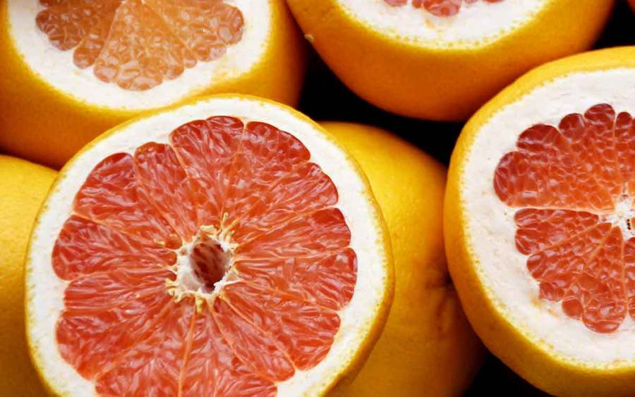 Pink and orange grapefruit and citrus fruits represent the types of superfoods you can plant in your garden.