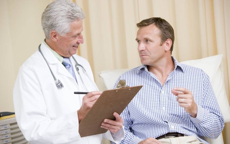 Physician and patient discussing difference between a colonoscopy and a sigmoidoscopy