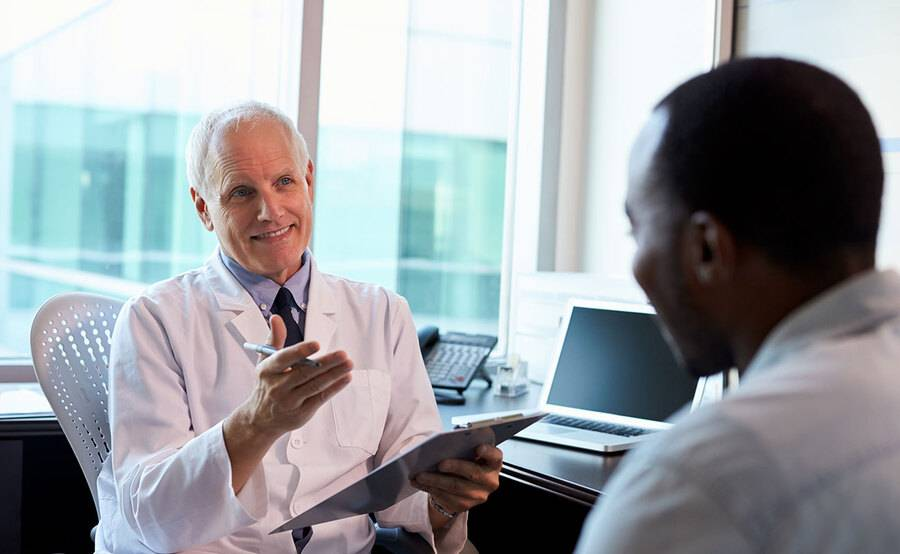 A physician talks to a 40-year-old man in a doctor's office.