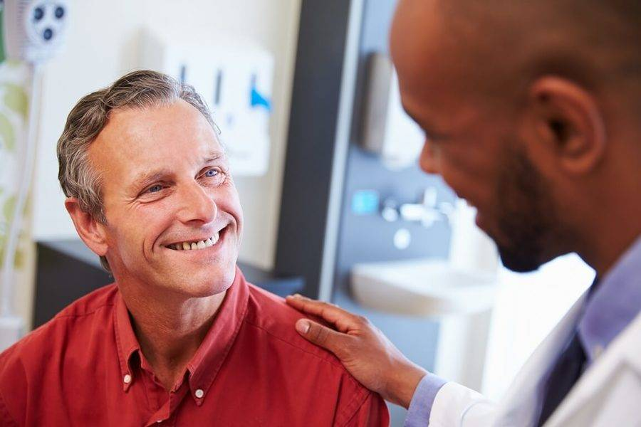 A doctor reassures a mature man in a red oxford shirt as they discuss five keys to a colorectal cancer screening.