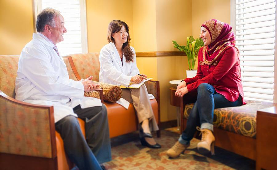 A doctor and nurse talk with a woman in a patient care setting, similar to the interactions between patients and providers who are part of the nurse navigator program at Scripps MD Anderson Cancer Center.