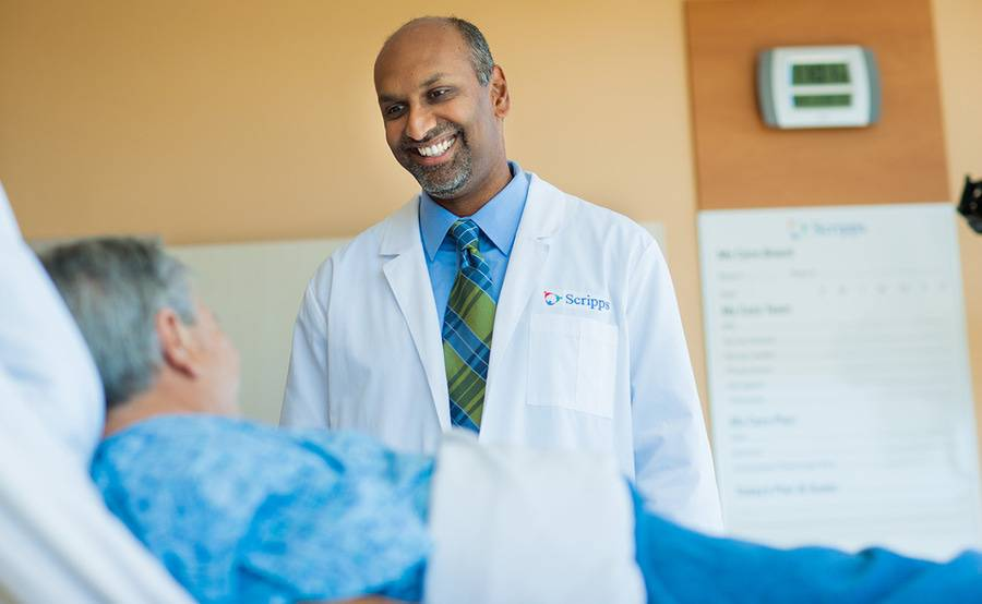 Dr. Sunil Rayan, a Scripps vascular surgeon, smiles during a conversation with a patient, representing care at Scripps for congenital heart defects.