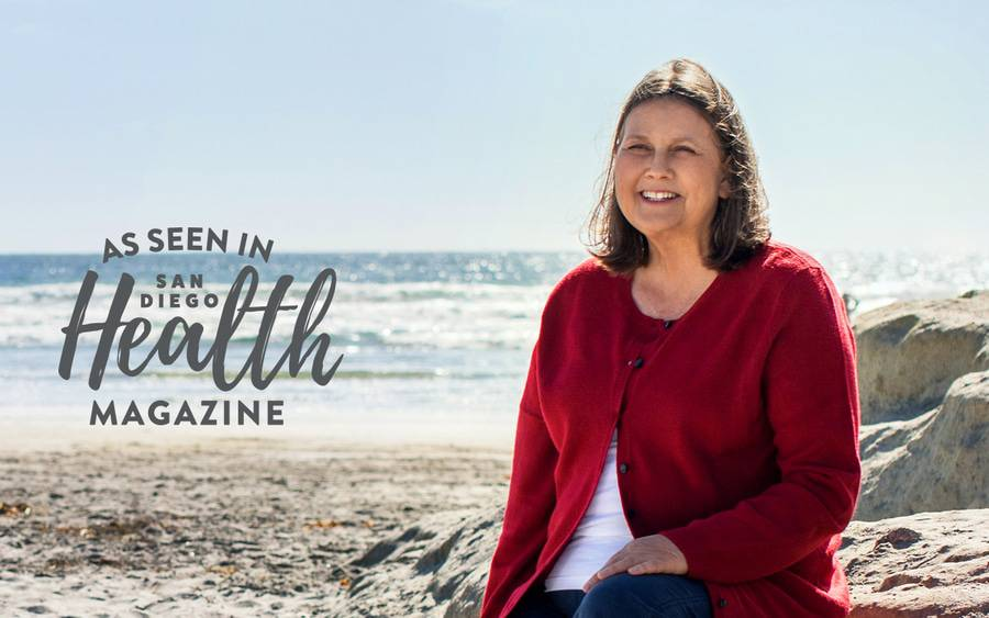 Kim Trauth sits on a beach after an innovative heart procedure at Scripps.