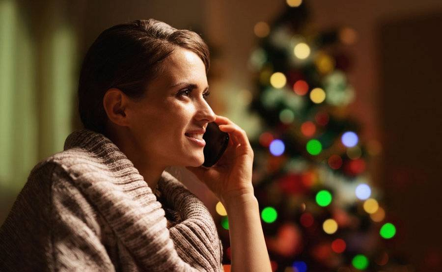 Grieving woman on the phone during holidays with decorated Christmas tree in the background.