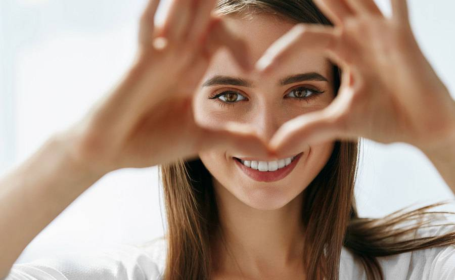 A young woman looks through her hands that are held up in the shape of a heart, representing the naturally beautiful appearance after cosmetic eye surgery.
