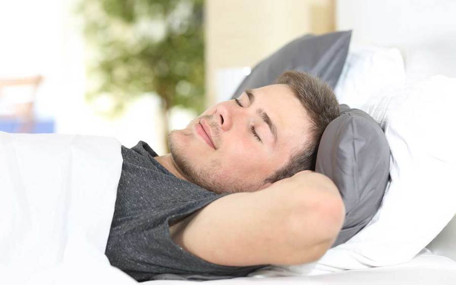A relaxed man sleeps in a comfortable bed.