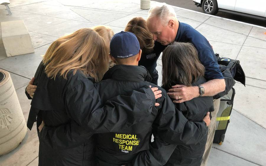 At San Diego airport, Chris Van Gorder, Scripps Health's president and CEO, huddles with members of Scripps nurses heading to Northern California to help fire victims.